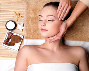 Pampering and massage for beautiful face of young woman in spa salon - indoors